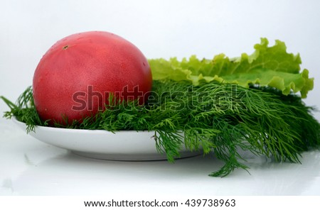 One ripe red tomato lying on a sheet of lettuce in a dish with dill Ukraine - stock photo