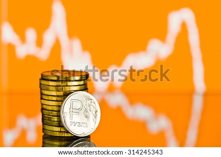 One rouble coin and gold money. Fluctuating graph on yellow background. Rate of the Russian rouble (shallow DOF)  - stock photo
