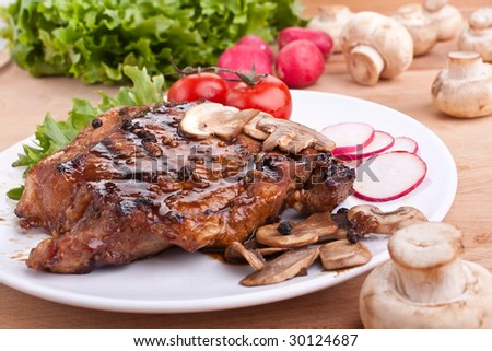 one serving of pork chop with mushrooms and radish - stock photo
