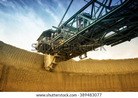 One side of huge coal mining digger machine photographed from a ground with wide angle lens. Dramatic and colorful sky in background. - stock photo