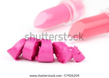 One sliced lipstick and two whole lipsticks in distance, closed-up on white - stock photo