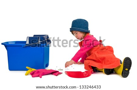 One small little girl wearing orange apron, red t-shirt, blue hat and yellow high boots, cleaning with red scoop and blue bucket. Isolated objects. - stock photo