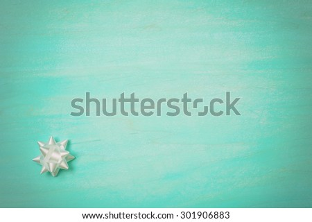 One Small, White Gift Bow in Lower corner on Cyan Painted Textured, Distressed Wood Board Background with Extra Room or Space for copy, text, your words.  Horizontal,  dark vignette for mood - stock photo