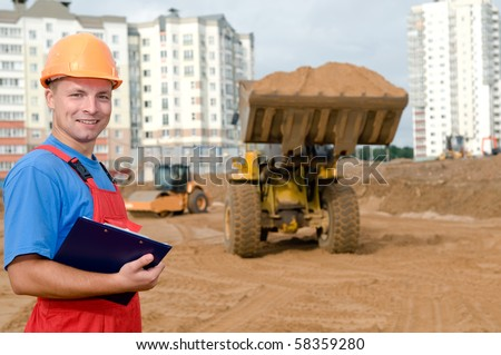 One smiley builder worker with clipboard inspecting earthmoving works at construction site - stock photo
