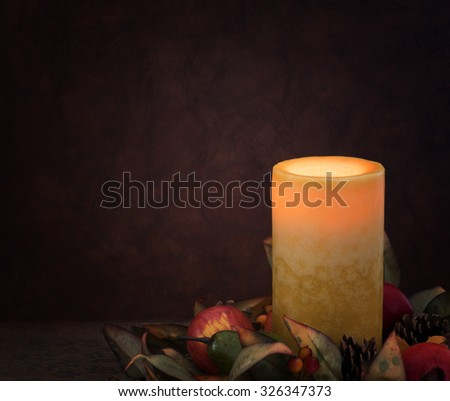 One Soft and Peaceful Fall Thanksgiving Yellow Candle glowing against Textured Wood Paneled Wall Background with room or space for copy, text, your words.  Horizontal with dark moody lighting  - stock photo
