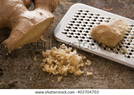 One stainless steel grater next to whole ginger root and shreds on a rustic table - stock photo