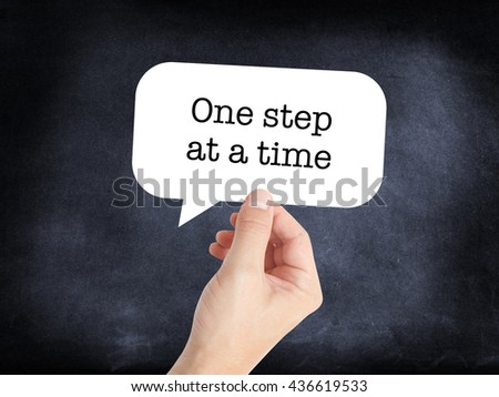 One step at a time written on a speechbubble - stock photo