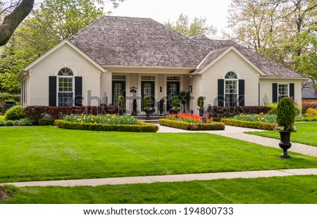 One storey house with a lawn and nice landscaping - stock photo
