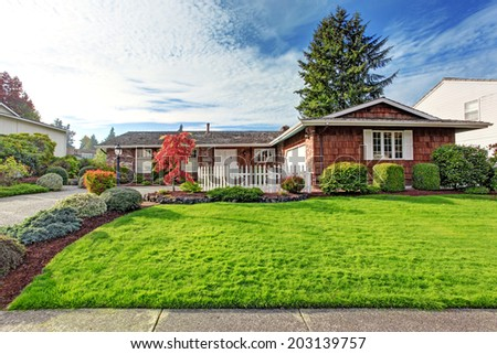 One story house with brick wall trim and clapboard siding. View of green front yard with white wooden fence - stock photo