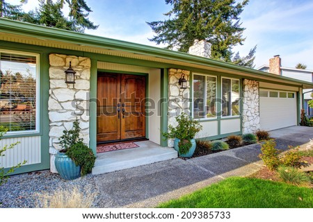 One story house with stone wall trim and garage. Entrance porch view - stock photo
