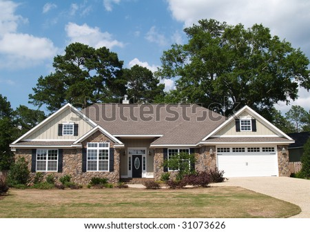 One story residential home with both stone and board siding on the facade. - stock photo