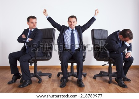 One successful businessman between two jealous businessman - stock photo