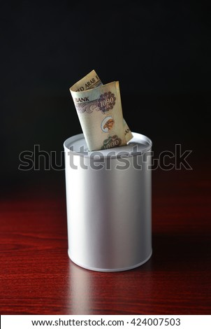 One thousand dirham note inserted in the saving can. Saving tin and UAE Dirham note. Stock photo. - stock photo