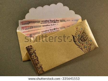 One thousand rupee notes in a decorative golden envelopes.  - stock photo