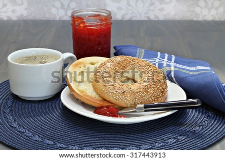 One toasted and buttered sesame bagel with homemade strawberry jam. - stock photo