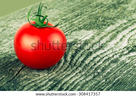 One tomato on old gray cracked wooden table. Background. Tinted. - stock photo