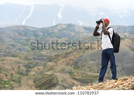 One tourist traveller hiker with binoculars in Himalayas mountains - stock photo