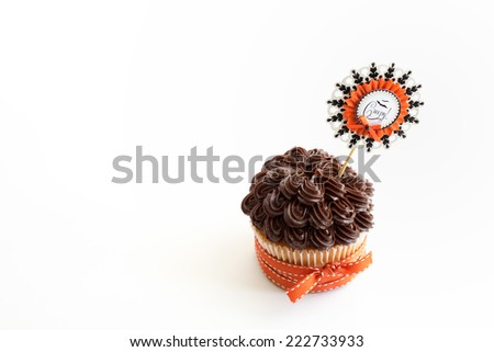 One vanilla cupcake with chocolate frosting decorated for Halloween with orange ribbon.  - stock photo