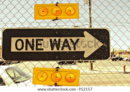 One-way street sign on chain link fence in inner city. - stock photo