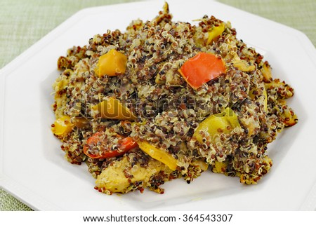 One white plate with cooked tricolor organic quinoa grain seed and a colorful mixture of red yellow and orange sweet bell peppers with purple onion for supper - stock photo