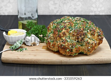 One whole head of roasted cauliflower on cutting board with roasting ingredients. - stock photo