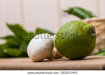 One whole juicy green lime with two raw unpeeled champignons on cutting plank on kitchen table, horizontal photo - stock photo