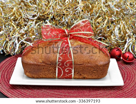 One whole loaf cake wrapped in a red and gold ribbon in front of gold tinsel.  A hostess gift for the holidays. - stock photo