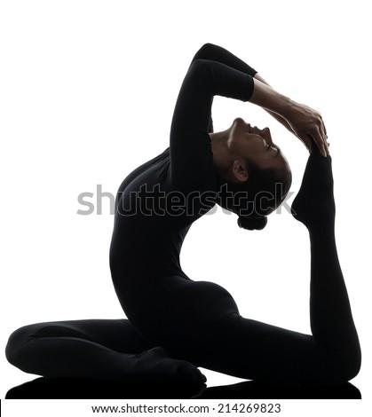 one  woman contortionist Eka Pada Rajakapotasana One Legged King Pigeon Pose yoga in silhouette on white background - stock photo