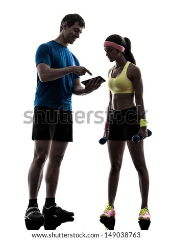 one  woman exercising fitness workout with man coach using digital tablet  in silhouette  on white background - stock photo