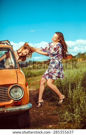 One woman is trying to pull another out of the car. - stock photo