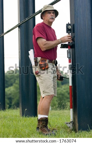One worker of a two man survey crew holds a prism at the foundation to record its position. He has rolled up blueprints in back pocket and various surveying tools on his utility belt. - stock photo