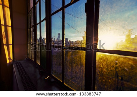 One World Trade Center (aka Freedom Tower) and Lower Manhattan skyline seen through soft focus angle of a window. Back lit by afternoon yellow sun on a rooftop West Village apartment. - stock photo