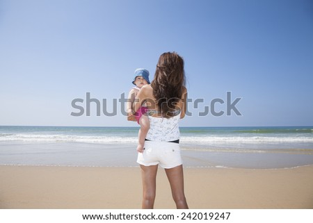 one year blonde baby in brunette woman mother arms back at beach Conil Cadiz Spain - stock photo