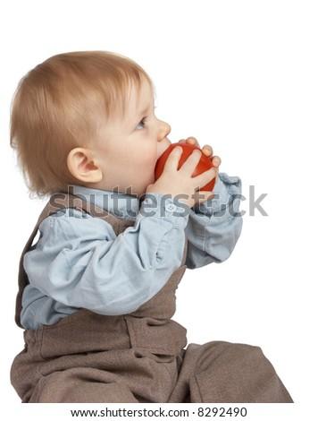 One-year boy eats a tomato. - stock photo