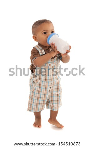 one year old baby boy holding milk bottle standing on isolated white background - stock photo