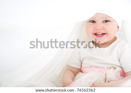 One year old baby girl wearing white and pink dress sitting in a white - stock photo