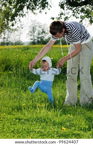 One year old baby learning to walk by holding his mother's hands - stock photo