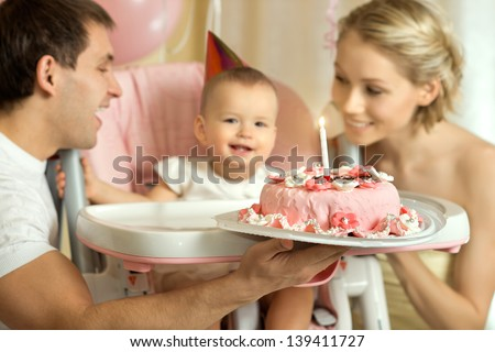 one-year-old little girl with daddy and mammy solemnize birthday, happy laughter, horizontal photo - stock photo