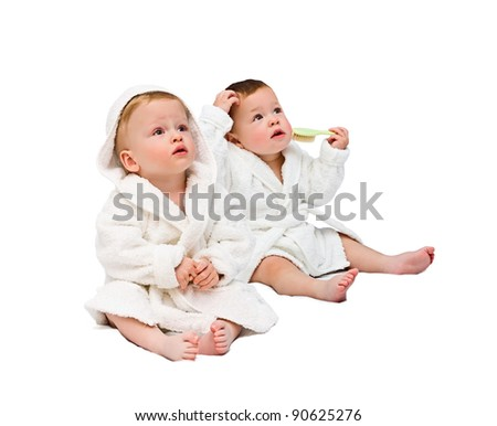 One-year-old twins in dressing gowns on a white background - stock photo
