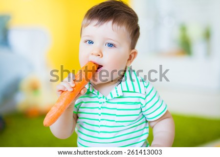 One years old boy eating fresh carrot - stock photo