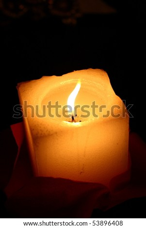 One yellow candle shines in dark. - stock photo