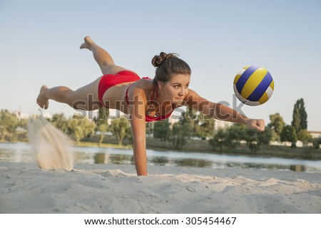 one young beautiful lady is playing volleyball on the beach, professional fly, summer time on beach. sport activity with red bikini making a save. - stock photo