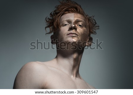 One young fashionable painted man model with bronzy bodyart on one half of face and stylish red hairdo looking forward standing in studio on grey background, horizontal picture - stock photo