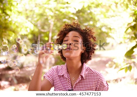 One young girl blowing bubbles with her eyes closed in the dappled afternoon sunshine with some trees around them wearing casual clothing - stock photo