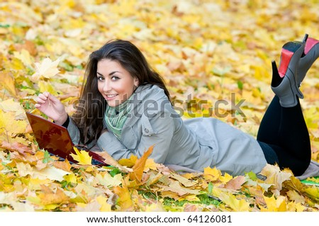 One young pretty student girl in yellow autumn leaves with computer laptop - stock photo
