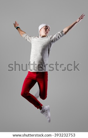 One young smiling modern style dancer guy in casual red jeans working out, dancing and jumping with open arms and funny serene facial expression. Full length photo, studio gray background - stock photo