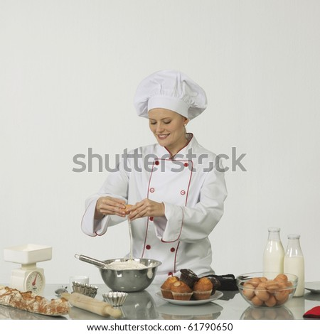 One young woman professional cook. She is braking an egg into a bowl of flour - stock photo
