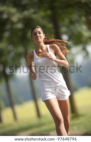 one young woman running outdoors in a sunny day - stock photo