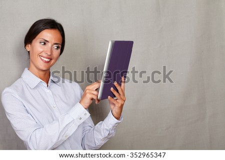 One young woman smiling and using tablet while wearing button down shirt on grey texture background - stock photo