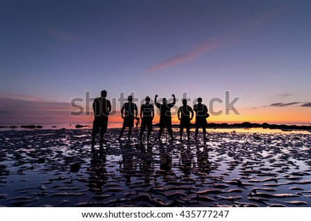 ong exposed seascape sunset with group unknow man sihleoutte at Matunggong, Kudat Sabah Malaysia. Image contain soft focus and blur. - stock photo
